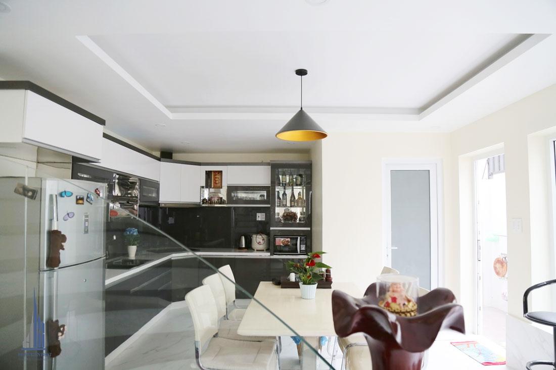 Không gian bếp được thiết kế hợp lí với hệ tủ chữ L và bộ bàn ăn gia đình hiện đại tiện nghi